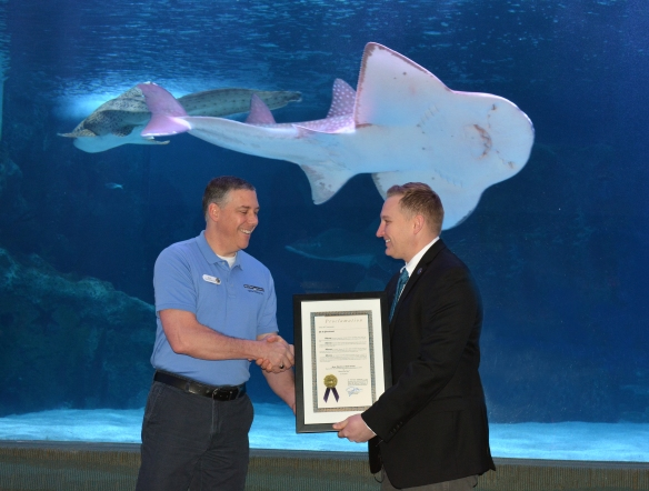 Newport Aquarium VP/Executive Director Eric Rose (left) and City of Cincinnati councilman Chris Seelbach shake hands during a mayoral proclamation presentation.
