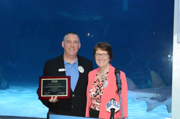 Newport Aquarium Executive Director Eric Rose (left) receives the aquarium's renewed accreditation from Association of Zoos & Aquarium Executive Director Kris Vehrs.